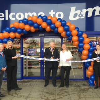 Lord Provost James Robertson joins Booby Mason from St Andrew's Hospice charity to cut the ribbon and officially re-open B&M Airdrie Retail Park store