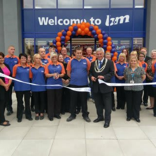 Mayor of Belper Gary Spendlove, supported by Sue Ryder charity, cuts the ribbon at B&M Belper store's re-opening, following a 9 month redevelopment.