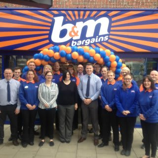 Store staff pose outside the brand new B&M Bargains Store in King's Lynn, Vancouver Centre.