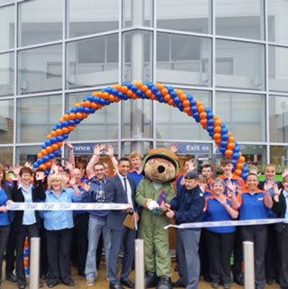 Elgin store being opened by the Help The Heroes Foundation representative FS Tony Walker with Cpl James Magee as their mascot bear who cut the ribbon.