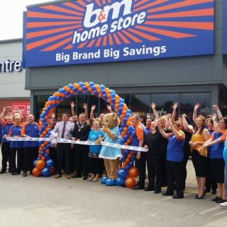 Deputy Mayor of Wirral, Pat Hacket cuts the ribbon at the opening ceremony of B&M's new Home Store & Garden Centre in Bromborough, Tebay Retail Park. Representatives from Claire House, including the Claire Bear mascot were also present and received £250 worth of B&M vouchers as a thank you.