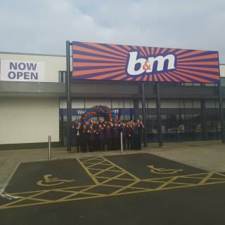 The store team at B&M's newest store in Breightmet pose in front of their wonderful new store, located on Bury Road.