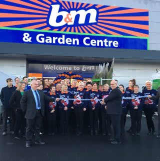 Store staff pose with Mayor of Featherstone, Cllr Steve Vickers as he cuts the ribbon at B&M's new Featherstone store.