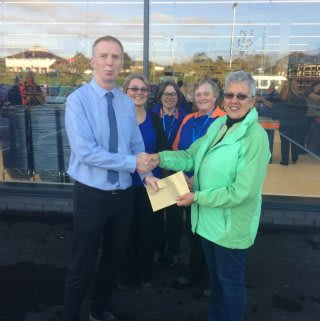 Representatives Teresa and Donna from the Wadebridge Food Bank charity accept £250 worth of B&M vouchers from store manager Jake Smith.
