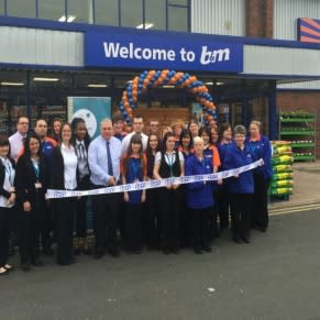 Minworth store manager Gary Rogers is joined by representatives from John Taylor Hospice who cut the ribbon on a landmark day for B&M